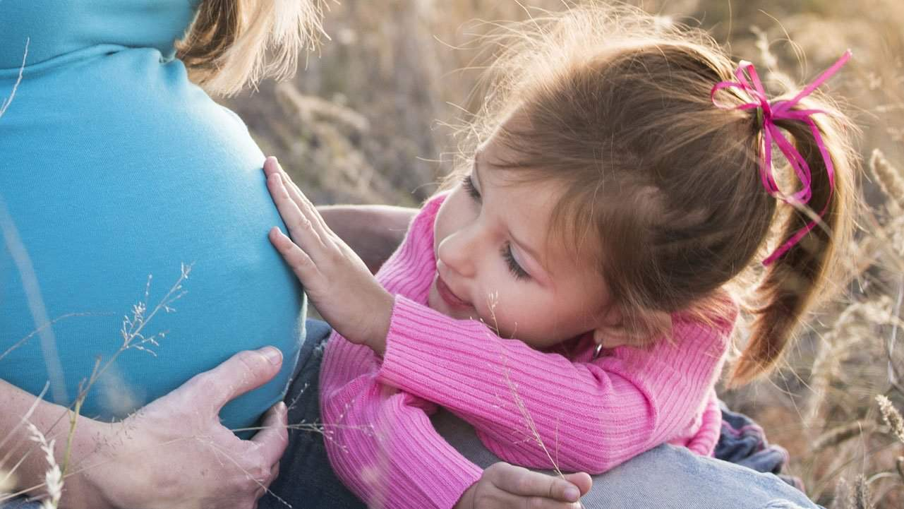 Young daughter touching mothers twin pregnancy belly
