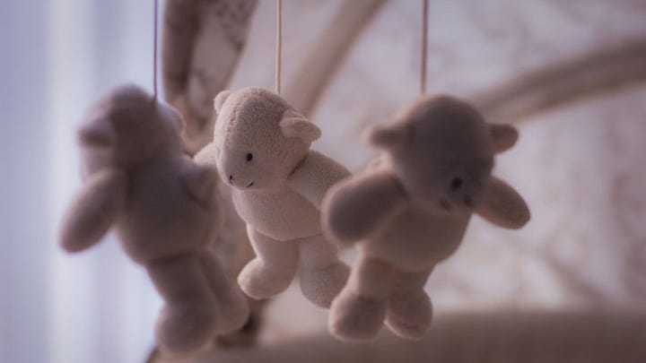 teddy bears hanging over crib