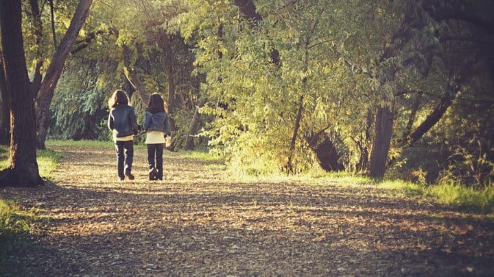 twin girls walking in the woods