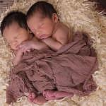 Twin babies sleeping on blanket