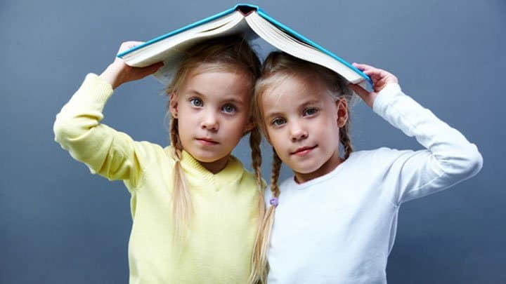 Twin girls holding book