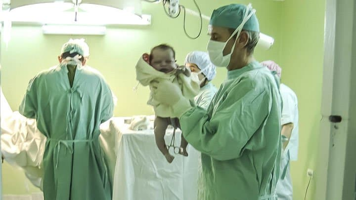 Newborn in delivery room held by doctor