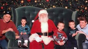Identical twins with family and Santa
