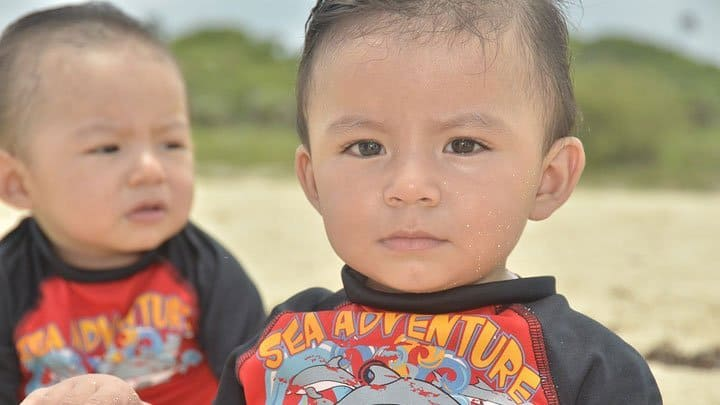 Identical twin boy toddlers at beach