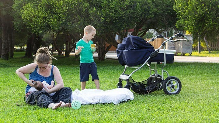 Mom nursing twins in park