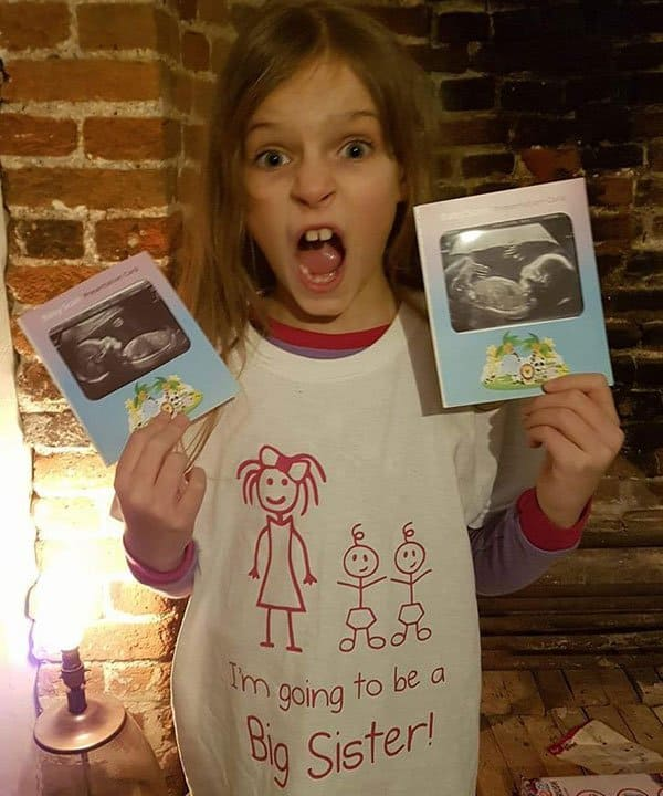 Big sister holding twin ultrasound scan pictures for twin pregnancy announcement