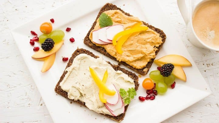 Rye bread and fruit on plate with coffee