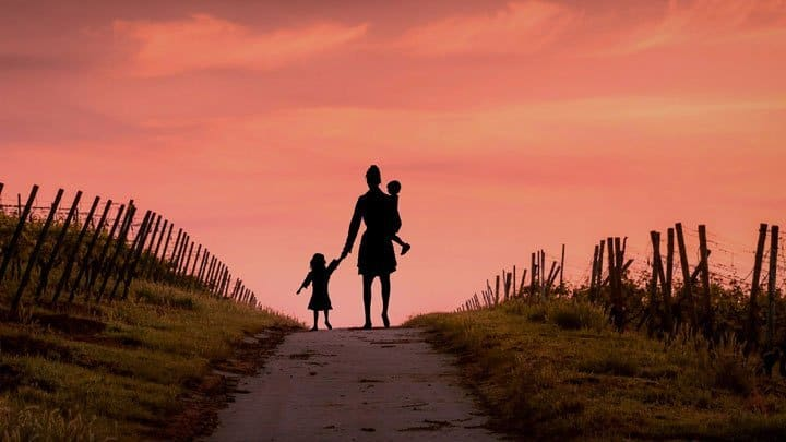 Mother walking with her children towards sunset